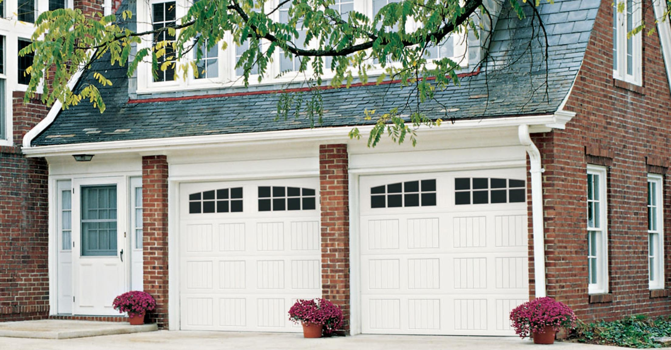 Brick home with white new garage doors